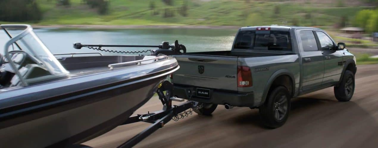 A green 2022 Ram 1500 is shown towing a boat.