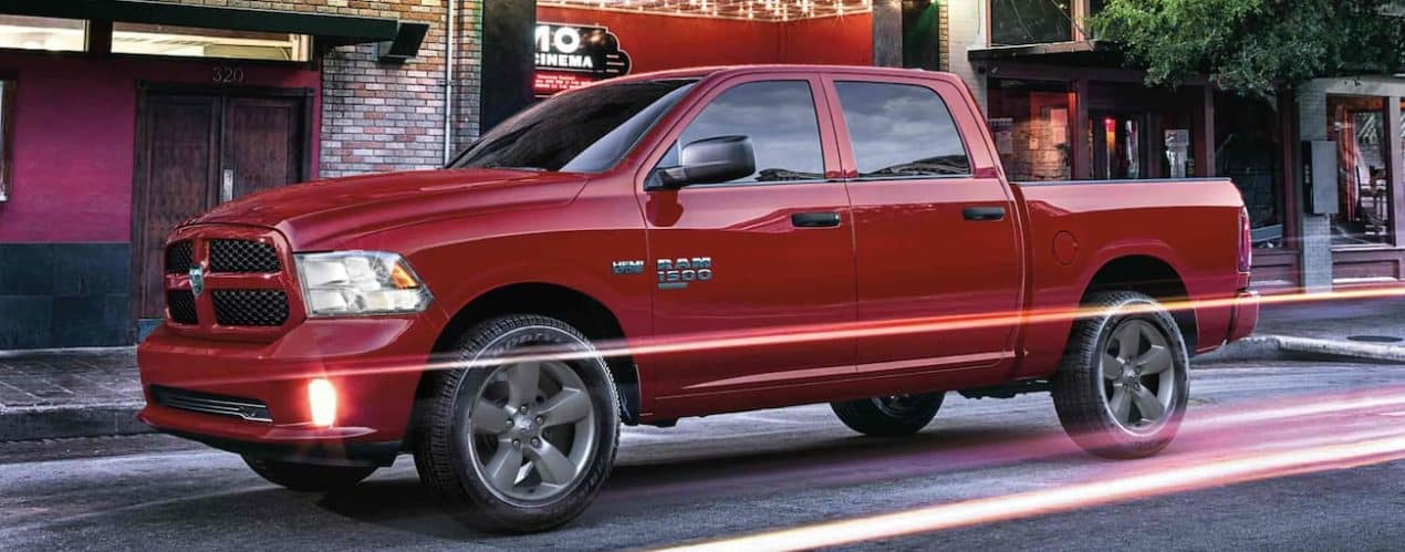 A red 2022 Ram 1500 is shown from the side parked on a city street.