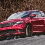 A red 2021 Jeep Grand Cherokee Trackhawk is shown driving on a race track from a low angle.